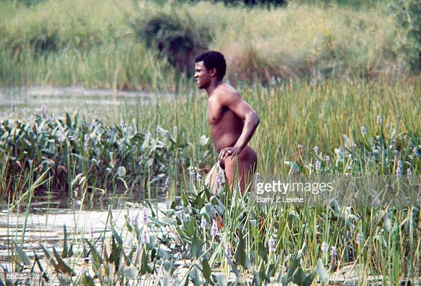 An African American male walking in the pond near the grounds of the Woodstock Music and Arts Fair in Bethel New York August 15 17 1969