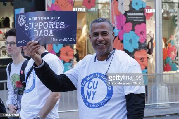 An African American man smiles and holds a sign in support of Deferred Action of Childhood Arrivals during the 2017 Labor Day Parade on Fifth Avenue...
