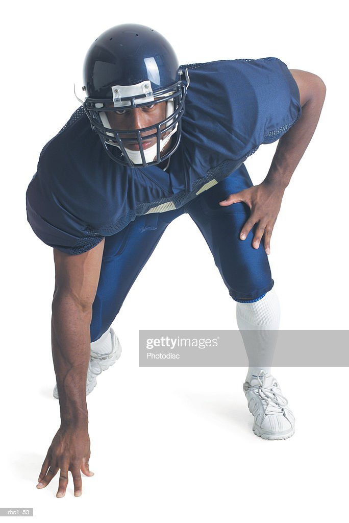 an african american man wearing a blue football uniform is crouching forward as her looks into the camera
