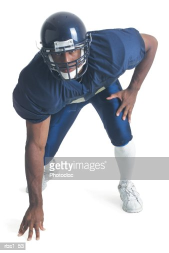 an african american man wearing a blue football uniform is crouching forward as her looks into the camera : Stock Photo