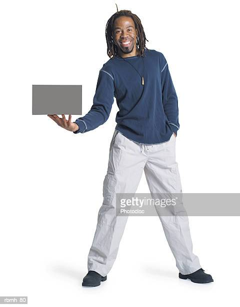 an african american man with dreadlocks wearing kakhi pants and a blue shirt holds a blank sign out to the side of him with one hand and he has his other hand in his pocket