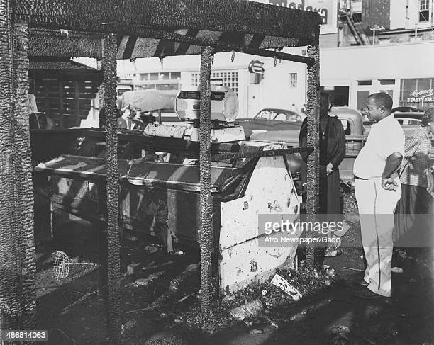 An African American shopkeeper examines the remains of his burned storefront stall at the Lafayette Market food and grocery market Baltimore Maryland...
