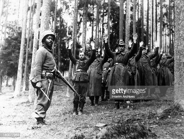 An African American soldier of the 12th Armored Division stands guard over a group of Nazi prisoners captured in the surrounding German forest April...