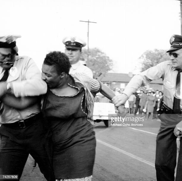 An African American woman bites a policeman during a protest against segregation organized by Reverend Dr Martin Luther King Jr and Reverend Fred...