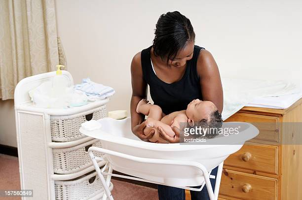 An African American Woman Lowering Baby Into Bath