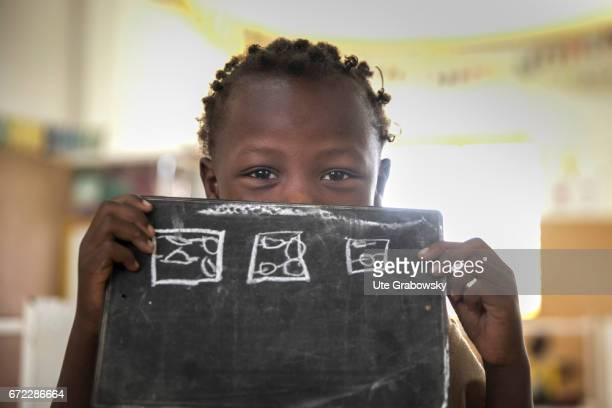 An African child poses in a classroom at a school of the Dreyer Foundation and holds a chalkboard in his hands Here children are cared for and will...