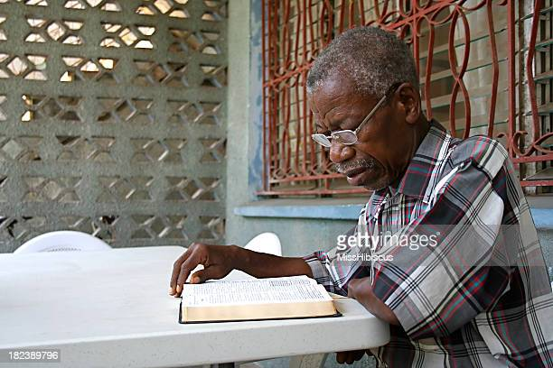 An African elderly gentleman reading a Bible