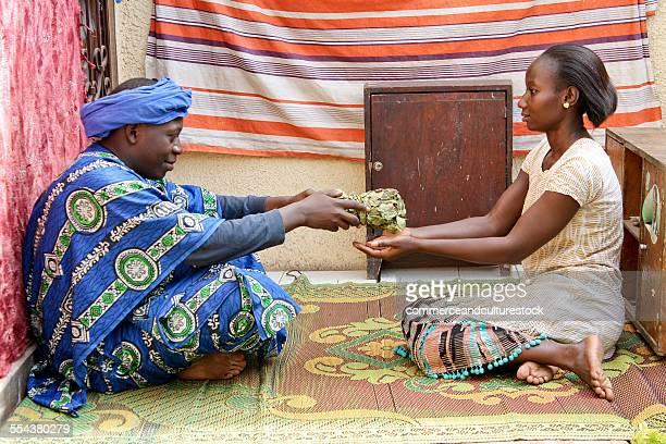 An african healer giving medicine to a woman