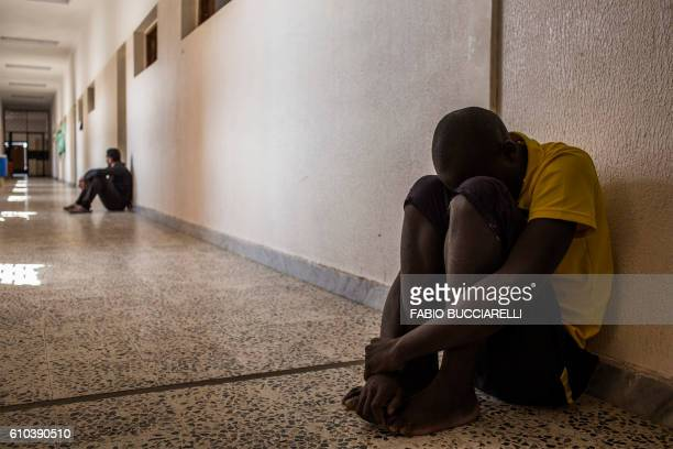 TOPSHOT An African migrant coming from Ivory Coast rests at Libya's Karareem detention centre near Misrata a town halfway between Sirte and Tripoli...