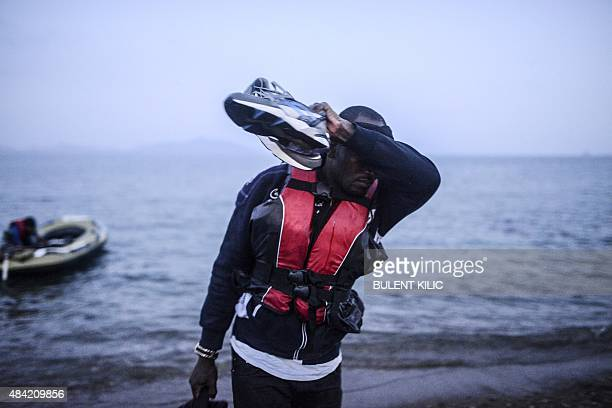 An African migrant walks back to the shore after failing to board a boat to the Greek island of Kos on early August 16 2015 off the shore of Bodrum...