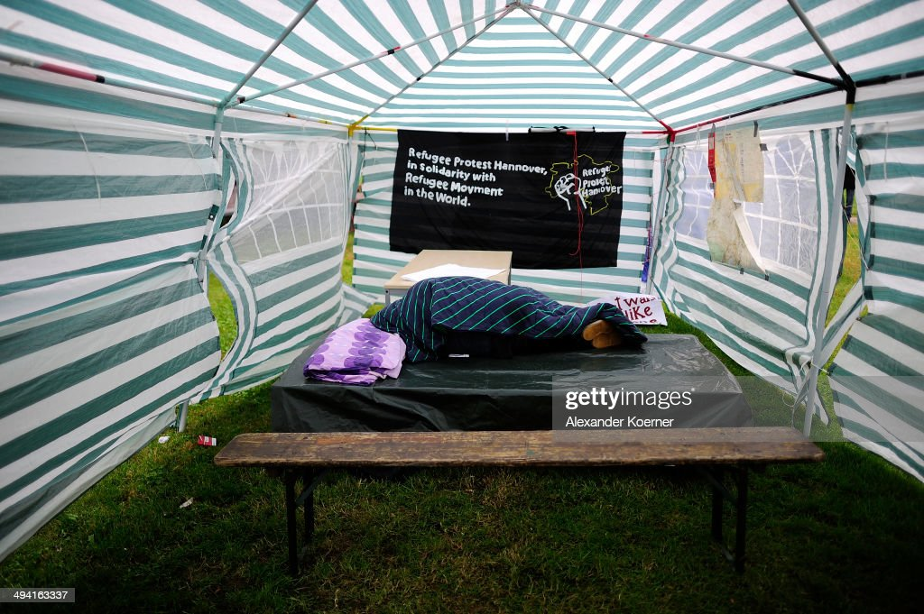 An African migrants sleeps inside a tent, while police forces dismantle tents, which were set up illegally by African migrants on the White Cross Square (Weissekreuzplatz) in the Oststadt district on May 28, 2014 in Hanover, Germany. Around 30 African migrants and 20 supporters had setup the protest camp on Saturday to protest against the asylum policy of the German Federal Republic and call for fair and equal treatment of all asylum seekers. The Police operation was completed peacefully.