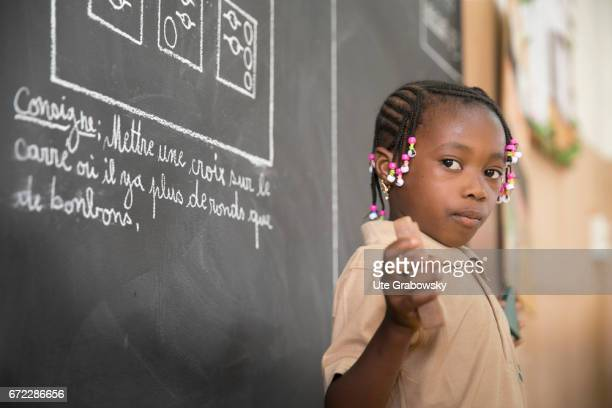 An African schoolgirl is standing in front of a blackboard in a school of the Dreyer Foundation Here children are cared for and will be promoted The...