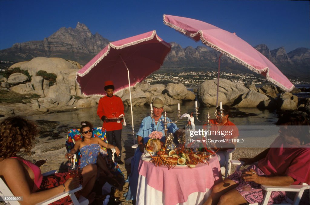 An African waiter serves drinks at a beach party on Clifton Beach, Cape Town, South Africa, circa 1990.