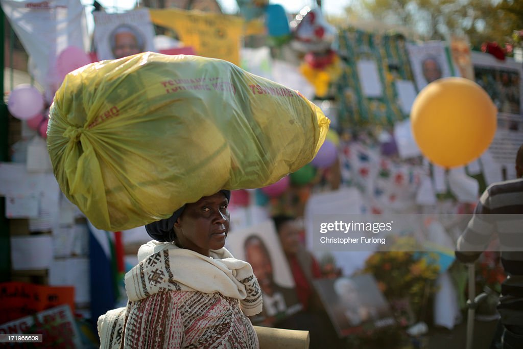 An African woman reads the tributes and messages of hope for former South African President Nelson Mandela outside the Mediclinic Heart Hospital where he is being treated for a recurring lung infection June 30, 2013 in Pretoria, South Africa. The anti-apartheid icon and Nobel Peace Prize laureate has been in the hospital for three weeks where his condition has been described as 'critical but stable.'