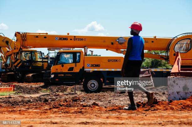 An African worker passes a Chinesemade XCMG Construction Machinery Co Ltd QY25KII all terrain truck crane at the construction site for a hydro...