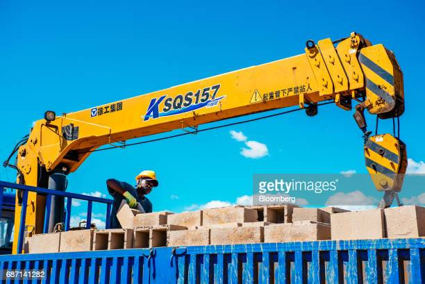 An African worker unloads building blocks from a truck at the construction site for a hydro pumping station which will supply water from the Limpopo...