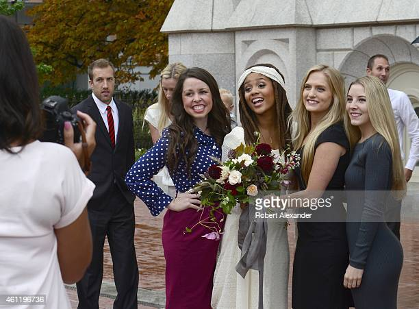 An AfricanAmerican bride poses for a photograph with friends after her wedding ceremony in the Salt Lake Mormon Temple in Salt Lake City Utah Once...