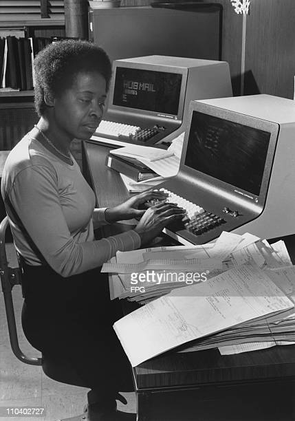 An AfricanAmerican office worker logs addresses into a Data General computer at a directmail company in Boston Massachusetts circa 1980