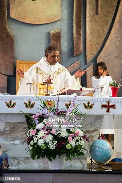 An AfricanAmerican priest delivers a religious ceremony in traditional vestments while a young girl assists