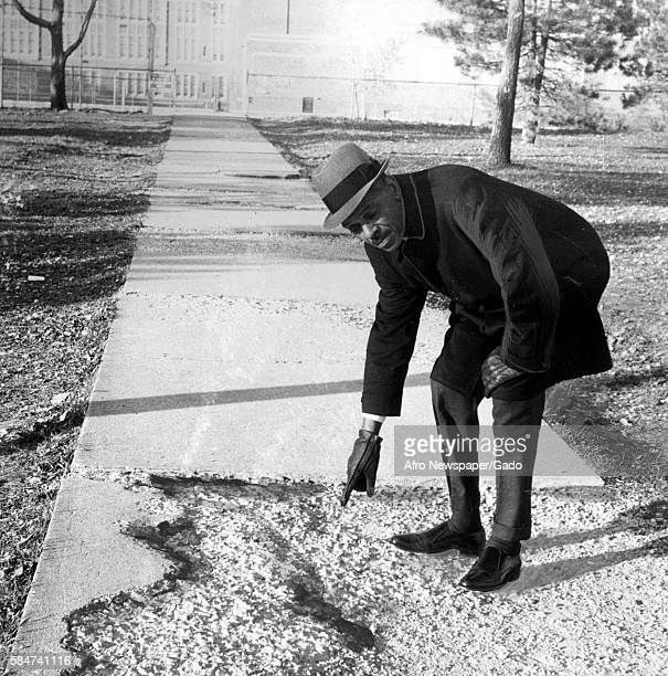 An AfricanAmerican reverend points out cracked cement at Douglass High School in Baltimore Maryland while protesting the city's failure to maintain...