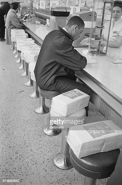 An AfricanAmerican student sits at a lunch counter reserved for white customers during a sitin to protest segregation Packages of napkins have been...