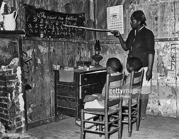 An AfricanAmerican woman teaching two young boys to read in a makeshift classroom in a rural part of the southern USA January 1939