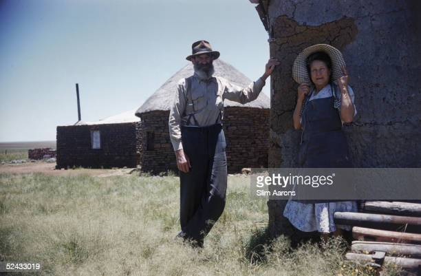 An Afrikaaner couple pose by a stone outhouse at their farm in South Africa December 1958