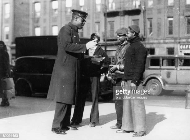 An afroamerican policeman in Harlem in debate with three juveniles New York USA Photograph Around 1930 [Ein afroamerikanischer Polizist in Harlem im...