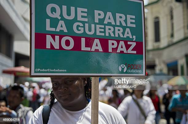 An AfroColombian woman holds a sign that reads 'Let war stop not peace' during the Peace Day in Cali Colombia on April 9 2015 The Colombian...