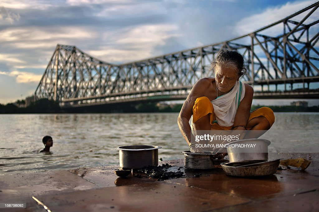 CONTENT] an aged woman washes utensils at mullick ghat on river ganges in kolkata while afternoon sunlight falls on her. famous howrah bridge can be seen from this ghat and the sight is beautiful. who: parbati, a local woman what: a local woman doing her daily chores with famous howrah bridge in backdrop in the afternoon where: kolkata, west bengal, india when: 3-sep-2011