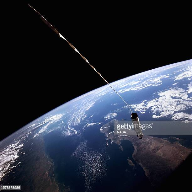 An Agena rocket is joined to the Gemini 12 spacecraft at the end of a long tether They have been joined to test a means of creating artificial...