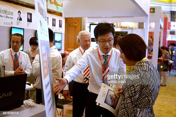 An agent for a US property investment company talks with a Chinese woman at an international property exhibition in Beijing on May 17 2014 Price...
