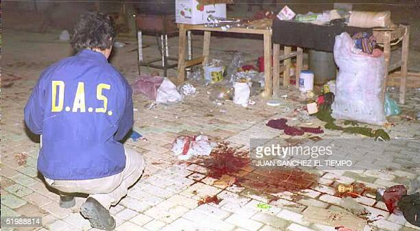 An agent of Colombia's Administrative Department of Security inspects early 11 June the site in downtown MedellinColombiawhere a powerfule bomb...