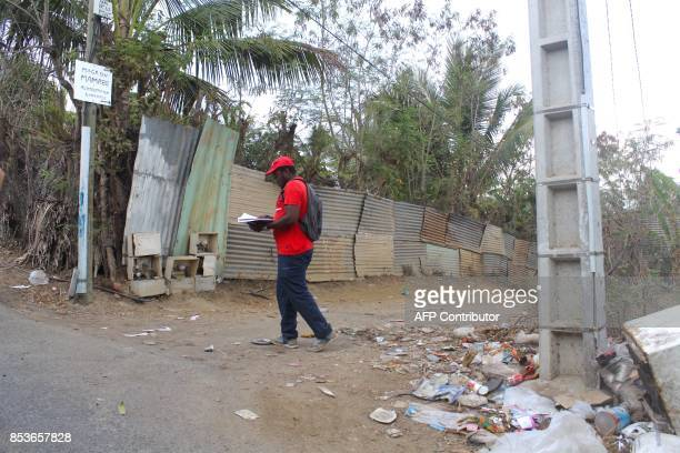 An agent of the census services walks in a street of La Vigie in PetiteTerre on the Mozambique channel French archipelago of Mayotte on September 22...