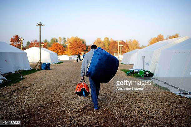 An Aghan refugee moves from a tent into a weatherresistant accommodation facility at a shelter for asylumseekers on October 27 2015 in Celle Germany...