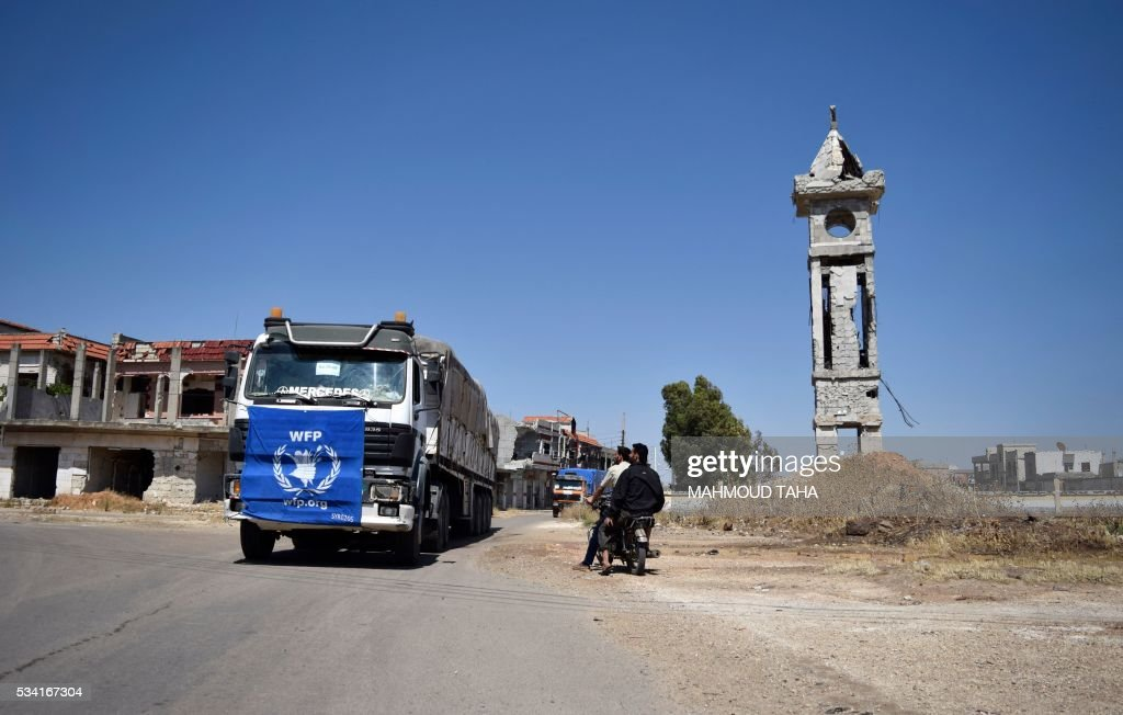 An aid truck of the UN World Food Programm (WFP) drives past destroyed buildings the town of Al-Houla, on the northern outskirts of Homs in central Syria, on May 25, 2016. / AFP / MAHMOUD