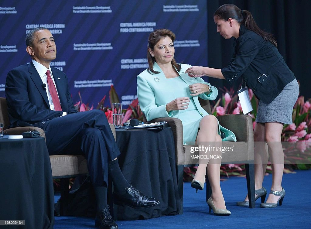 An aide adjusts the microphone of Costa Rica President Laura Chinchilla as US President Barack Obama (L) looks on during the Inclusive Economic Growth and Development forum at the Old Customs House in San Jose on May 4, 2013. Obama turned the spotlight on economic ties with Latin America on Saturday as he wrapped up a three-day trip to a region roiled by drug violence. Obama sought to shift the narrative away from the drug war during visits to Mexico and Costa Rica this week, praising trade as a path to fighting poverty and creating jobs that turn young people away from a life of crime. AFP PHOTO/Mandel NGAN