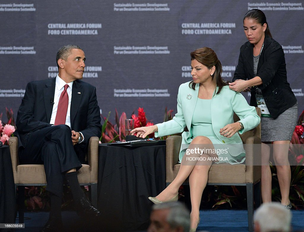 An aide adjusts the microphone of Costa Rica President Laura Chinchilla as US President Barack Obama (L) looks on during the Inclusive Economic Growth and Development forum at the Old Customs House in San Jose on May 4, 2013. Obama turned the spotlight on economic ties with Latin America on Saturday as he wrapped up a three-day trip to a region roiled by drug violence. Obama sought to shift the narrative away from the drug war during visits to Mexico and Costa Rica this week, praising trade as a path to fighting poverty and creating jobs that turn young people away from a life of crime. AFP PHOTO / Rodrigo ARANGUA