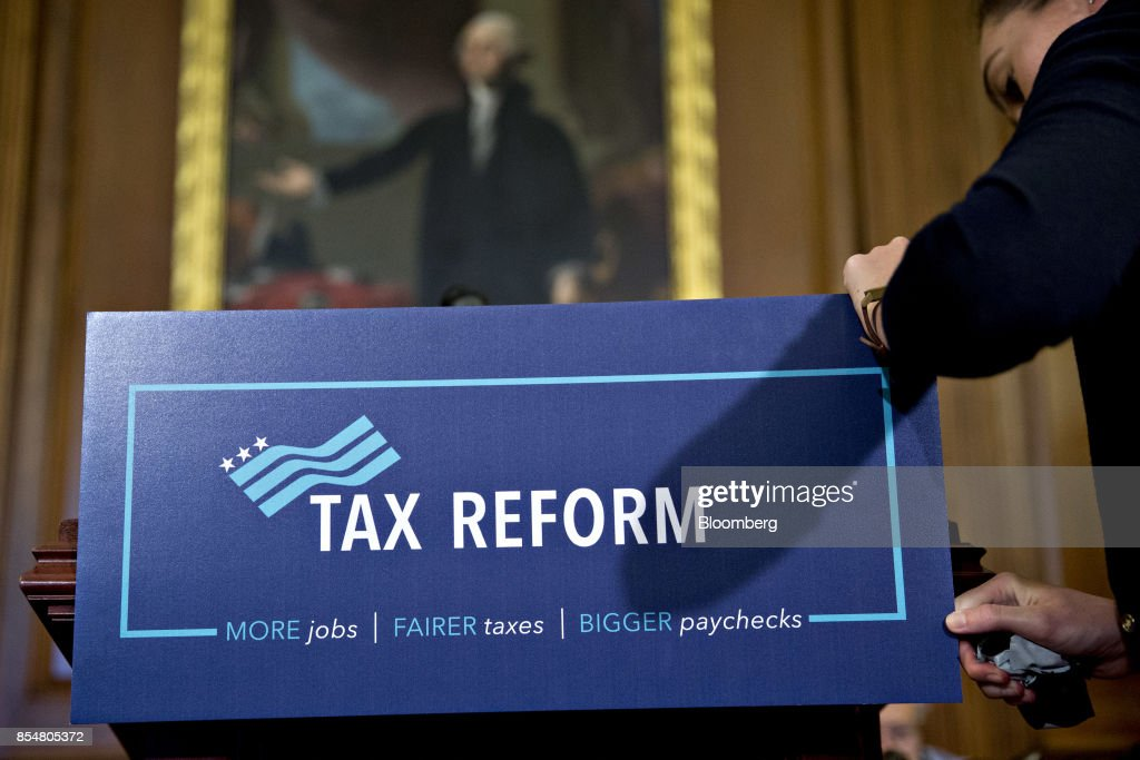 An aide from the office of U.S. House Speaker Paul Ryan removes a 'Tax Reform' sign from a podium after a news conference on a unified tax reform framework at the U.S. Capitol in Washington, D.C., U.S., on Wednesday, Sept. 27, 2017. President Donald Trump and congressional leaders are rolling out a framework for a tax overhaul that would condense the existing seven tax rates to three, and cut the top rate to 35 percent from 39.6 percent. Photographer: Andrew Harrer/Bloomberg via Getty Images