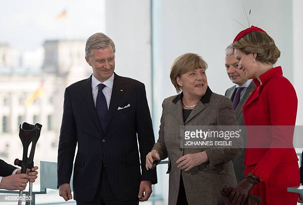 An aide hands German Chancellor Angela Merkel her crutches as she welcomes Belgian King Philippe and Queen Mathilde at the chancellery on February 17...