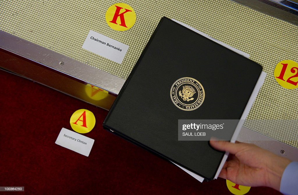 An aide picks up a binder bearing the seal of the President of the United States alongside the markers where US Secretary of State Hillary Clinton and Chairman of the Federal Reserve Ben Bernanke will stand for a family photo with US and Chinese officials at the Great Hall of the People in Beijing on May 24, 2010, during the start of the second round of the US-China Strategic & Economic Dialogue. The United States pessed China for joint action against North Korea at the start of high-level talks aimed at putting an end to months of discord, notably over currency and trade disputes. AFP PHOTO / POOL / Saul LOEB