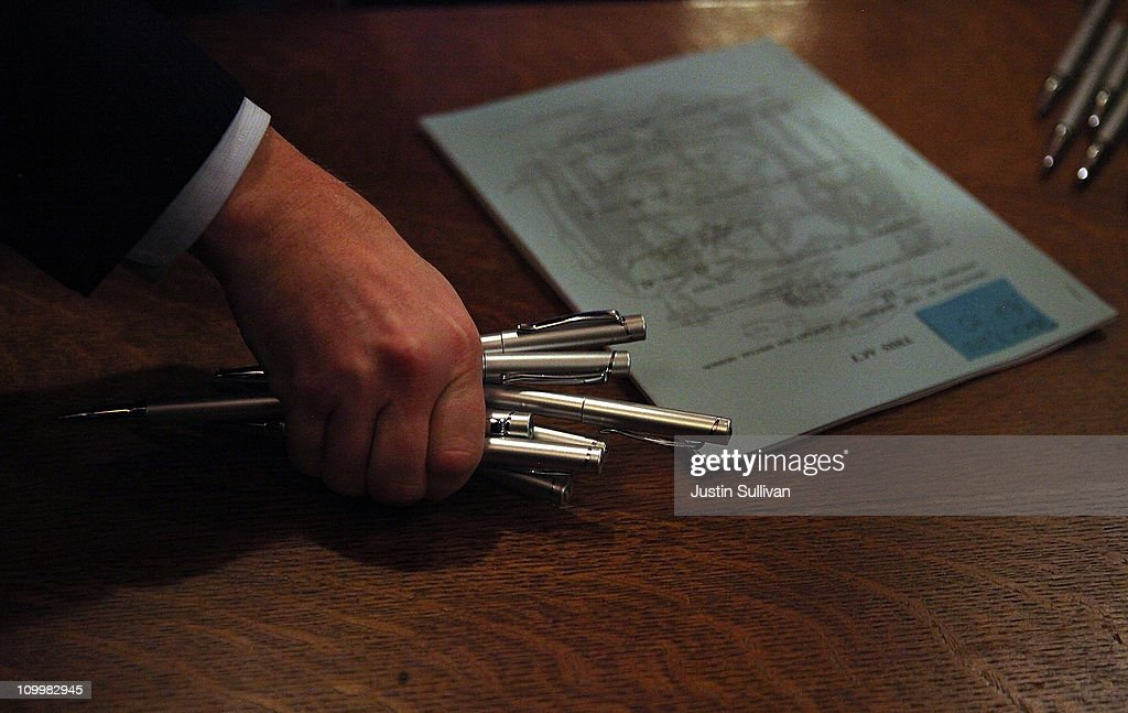 An aide to Wisconsin Gov Scott Walker picks up pens that were used during a ceremonial bill signing outside his office at the Wisconsin State Capitol...