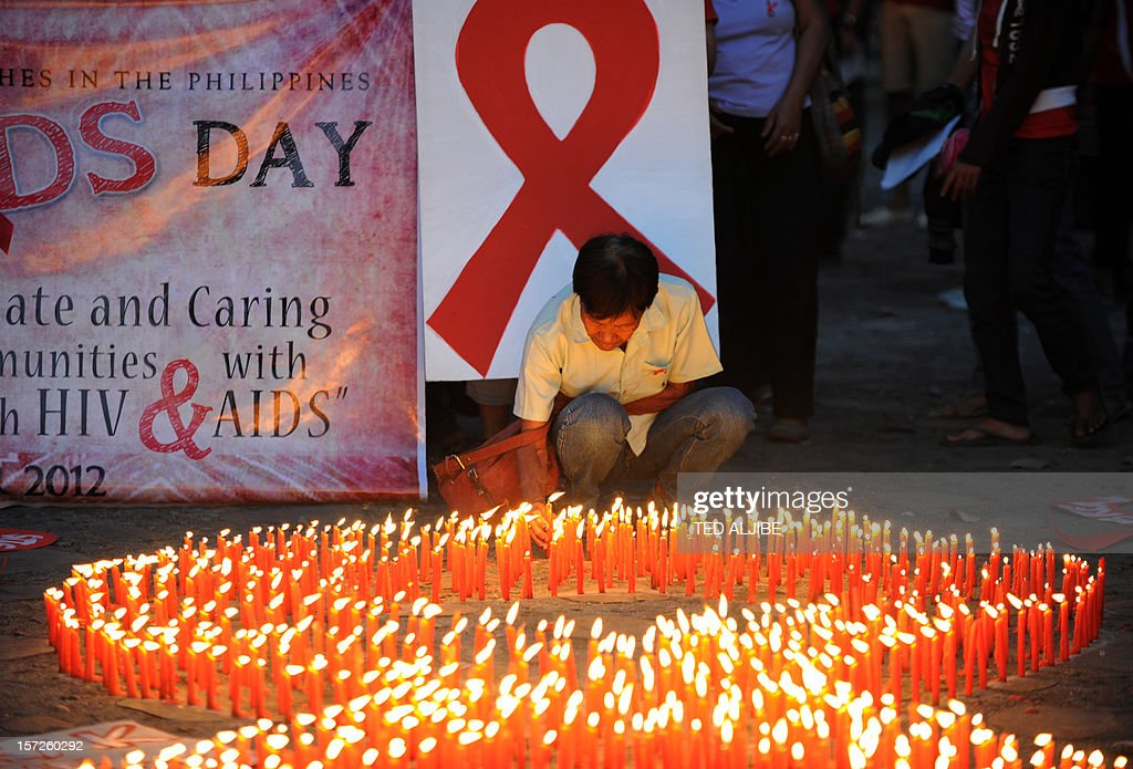 An AIDS activist lights a group of candles placed in the shape of a red ribbon during an event marking World Aids Day in Manila on December 1, 2012. Discrimination against homosexuals and people infected with HIV is contributing to the rapid rise of the incurable disease in the Philippines, officials and health activists said. AFP PHOTO/TED ALJIBE