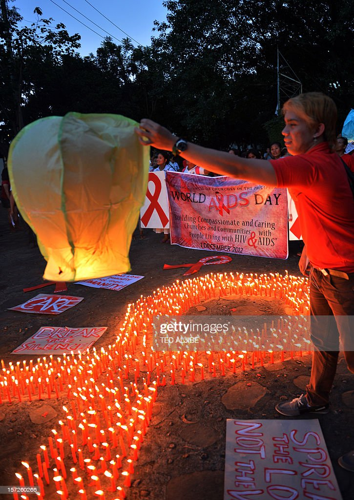An AIDS activist prepares to release a fire baloon next to lit candles formed in a red ribbon during an event marking World AIDS Day in Manila on December 1, 2012. Discrimination against homosexuals and people infected with HIV is contributing to the rapid rise of the incurable disease in the Philippines, officials and health activists said.