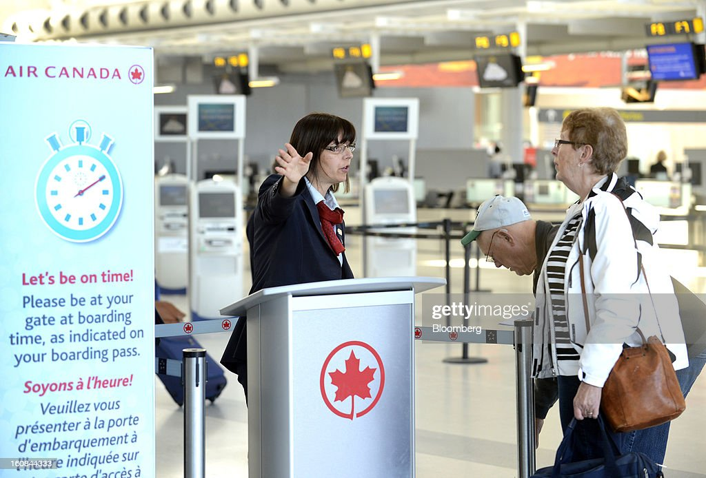 An Air Canada employee assists travelers at Pearson International Airport in Toronto, Ontario, Canada, on Wednesday, Feb. 6, 2013. Air Canada, the country's biggest carrier, is scheduled to announce quarterly earnings data on Feb. 7. Photographer: Aaron Harris/Bloomberg via Getty Images