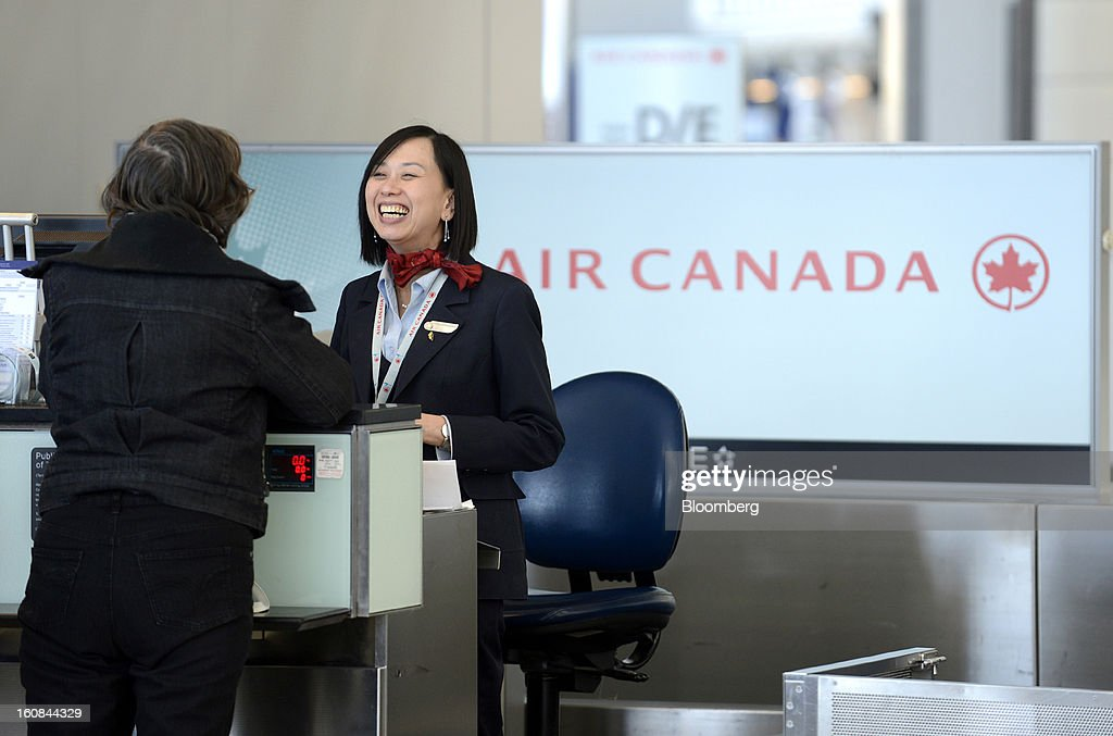 An Air Canada employee helps a traveler check-in at Pearson International Airport in Toronto, Ontario, Canada, on Wednesday, Feb. 6, 2013. Air Canada, the country's biggest carrier, is scheduled to announce quarterly earnings data on Feb. 7. Photographer: Aaron Harris/Bloomberg via Getty Images