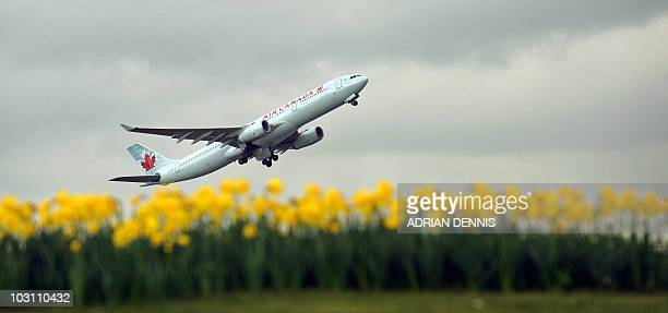 An Air Canada plane is pictured over a bed of daffodils as it takes off from London Heathrow Airport on March 25 2010 AFP PHOTO / Adrian Dennis