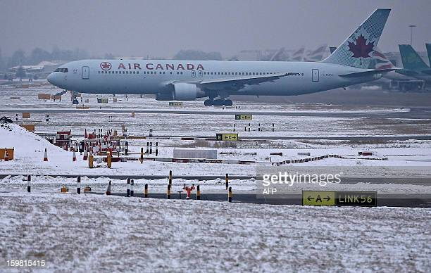 An Air Canada plane taxies on the snowy runway at Heathrow airport in west London on January 21 2013 after the airport announced further flight...