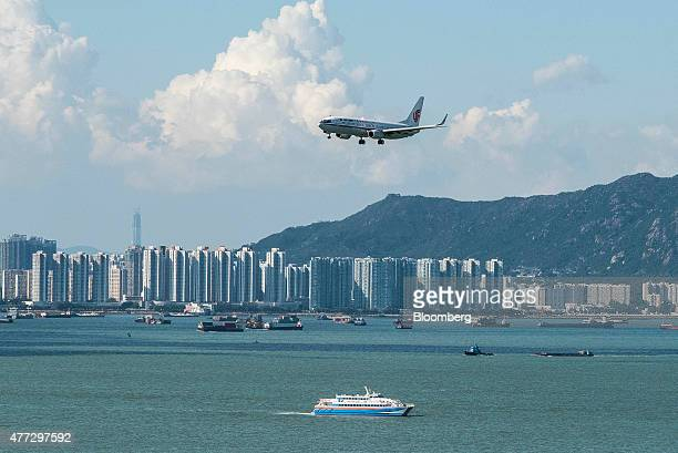 An Air China Ltd aircraft flies past residential buildings in the Tung Chung area as it approaches to land at Hong Kong International Airport in Hong...