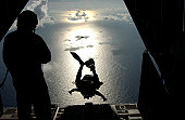 July 22, 2004 - An Air Force pararescueman jumps out of the back of an HC-130 Hercules during a rescue near the island of St. Maarten.  The airman is parachuting in to provide medical support to a Chi